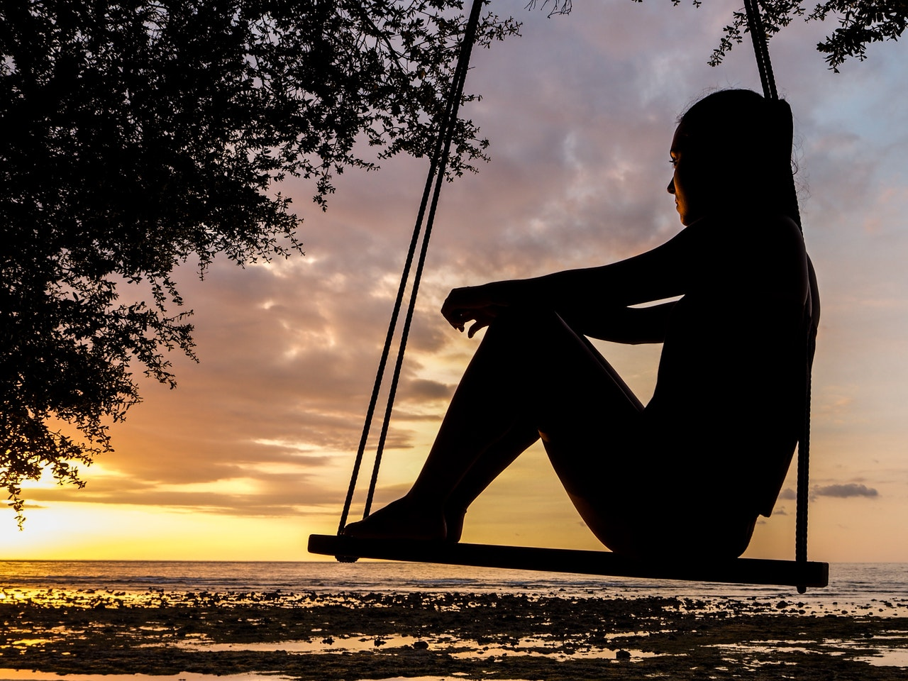 Silhouette of Woman thinking on Swing during Golden Hour