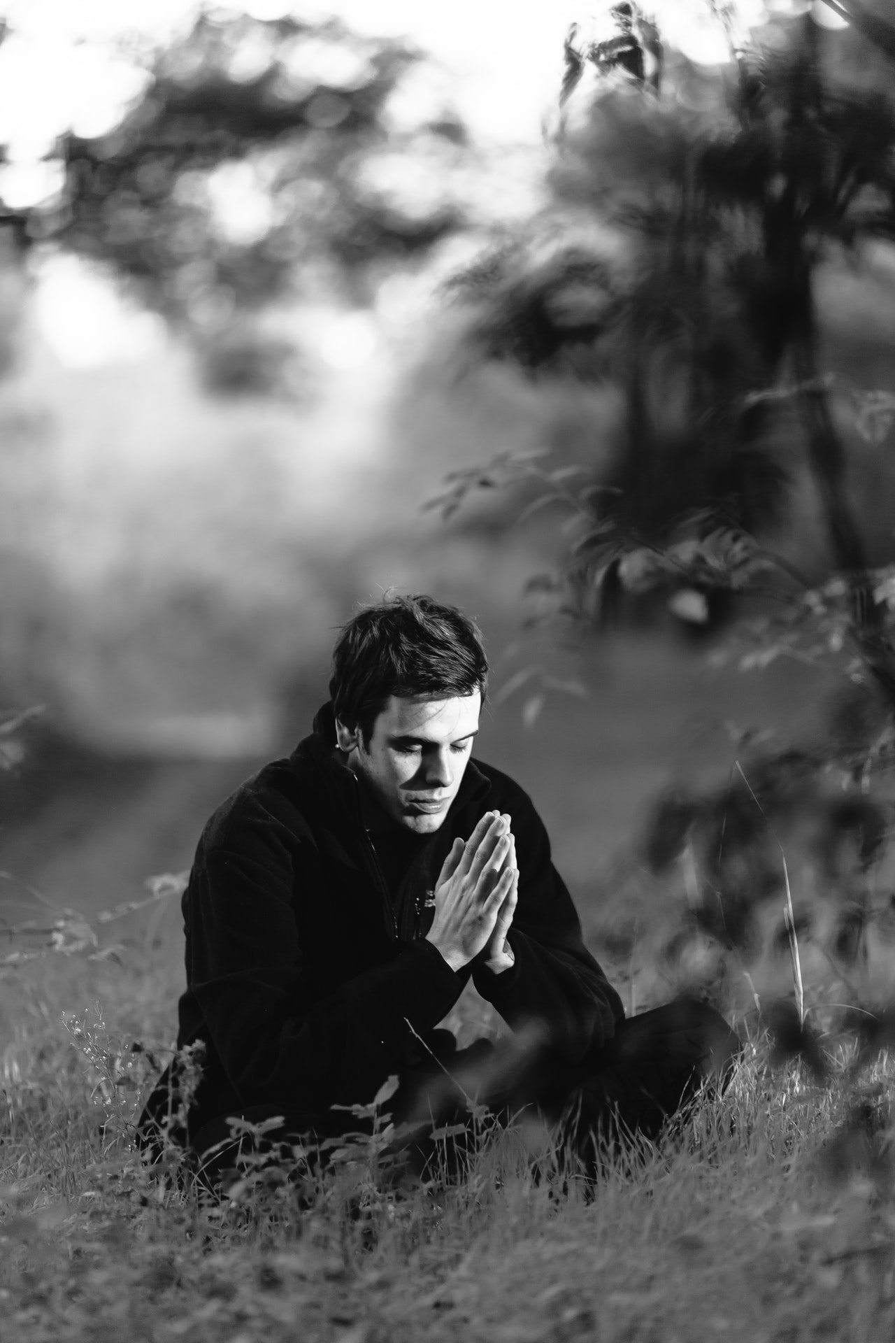 Man sitting on a grass field praying