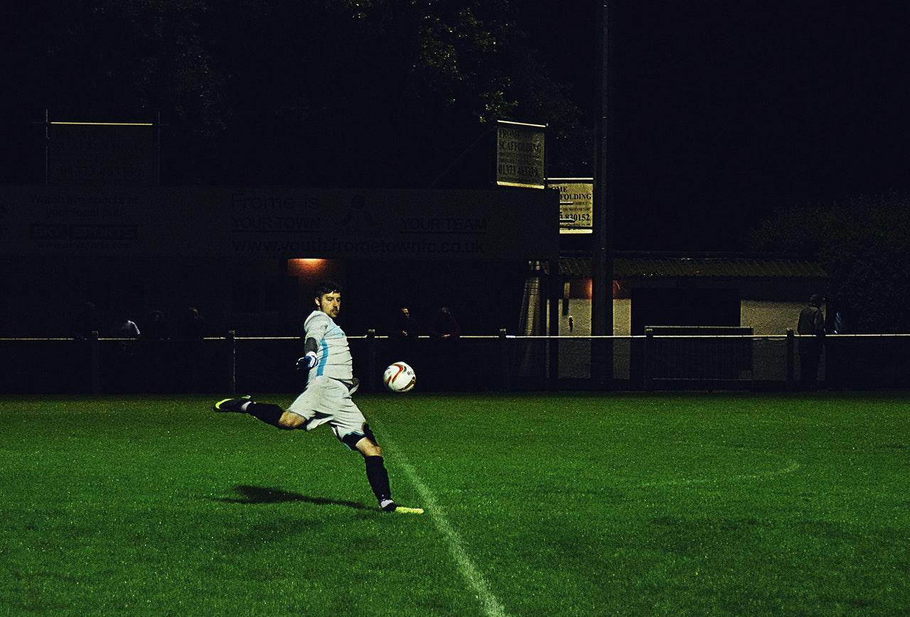 person kicks a soccer ball in field