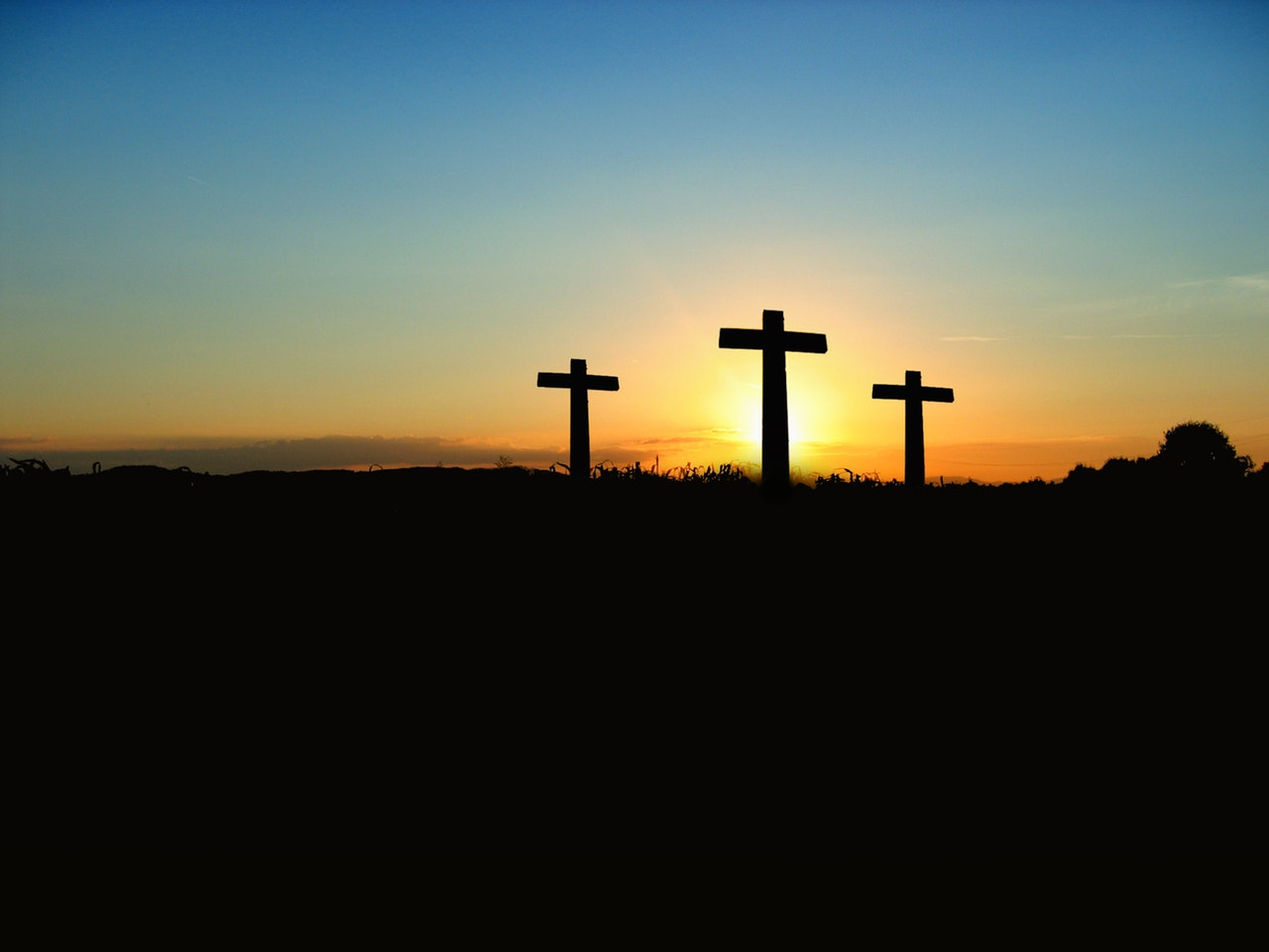 Silhouette of 3 crosses under the blue sky