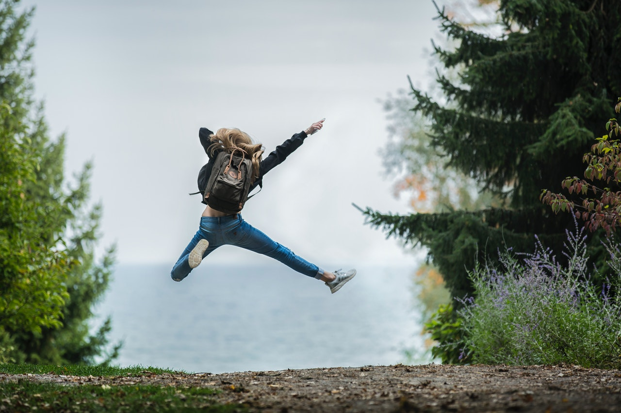Woman Jumping Freely Wearing Green Backpack