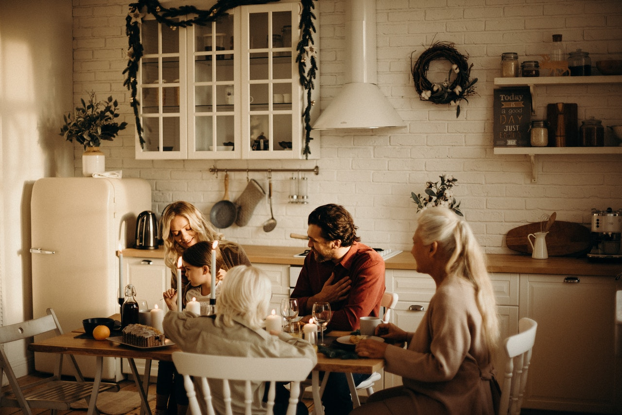 family sits around table inside kitchen
