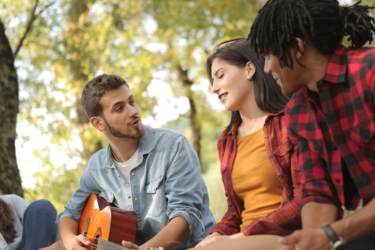 male with guitar singing worship songs with friends